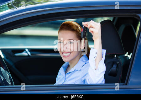 Closeup portrait happy, smiling, young, attractive woman, buyer sitting in her new black car showing keys isolated - Stock Photo