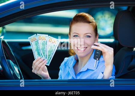 Closeup portrait happy smiling attractive woman sitting in her new black car showing keys, holding dollar bills - Stock Photo