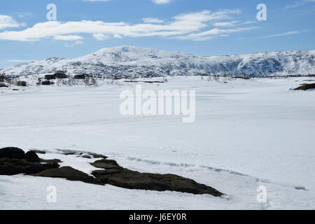 View over a frozen lake with snowmobile tracks and a Sami village and a snowy mountain in background, picture from - Stock Photo