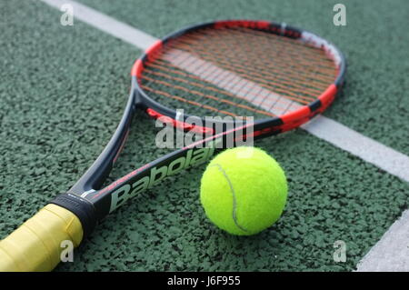 Tennis ball on a Babolat racquet on a hard court in London, UK - Stock Photo