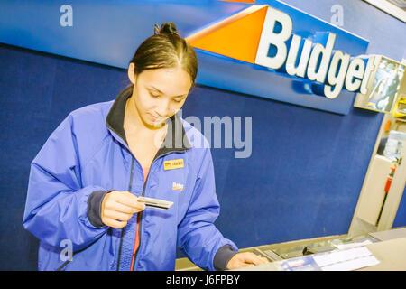 Florida Pensacola Pensacola Regional Airport trainee Budget Rent A Car Asian woman young adult counter worker job - Stock Photo