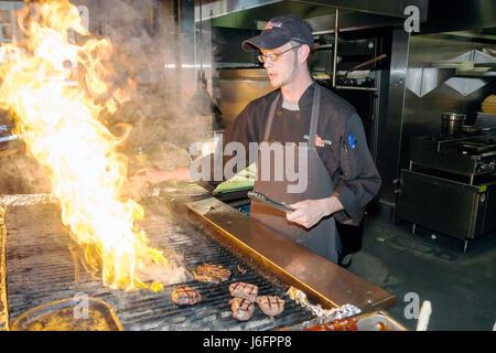 Tennessee Sevierville Kodak Chop House restaurant man cook work flames grill beefsteak food apron fire - Stock Photo
