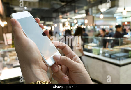 Hand holding mobile phone and abstract blur beautiful luxury food court in shopping mall and retail store interior for background