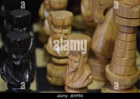 Carved chess pieces on a board, close-up. - Stock Photo