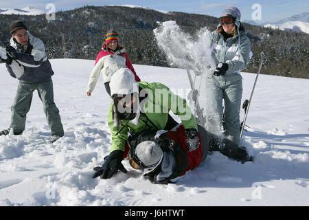 woman women men man friendship lie lying lies ski skiing snowball fight bicker - Stock Photo