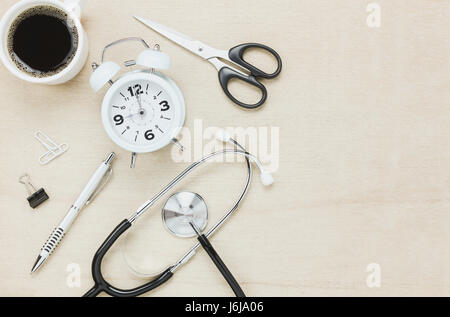 Top view stethoscope with clock coffee scissors with pen on wooden background. - Stock Photo