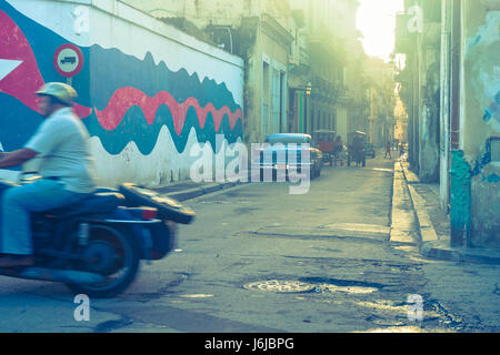 Gritty image back street motorcyclist passes out of frame in blurred movement while classic blue American car parked - Stock Photo
