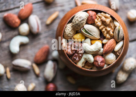 Dried mixed nuts in wooden bowl closeup. Walnut, pistachio, hazelnut, almond and other. Studio macro shoot. - Stock Photo