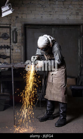 Young metalworker cutting on steel plate creating sparks, cutting iron with laser in workshop wearing protective - Stock Photo