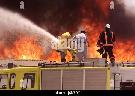 DUBAI, UNITED ARAB EMIRATES -31 JULY 2004:   Firefighters of the Dubai Civil Defence fight the blaze after a fire - Stock Photo