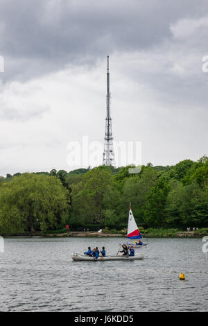People can be seen practicing sailing on South Norwood Lake on a Spring day while the Crystal Palace Transmitting - Stock Photo