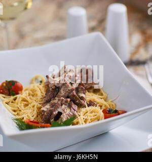 beef stroganoff with spaghettini in bowl - Stock Photo