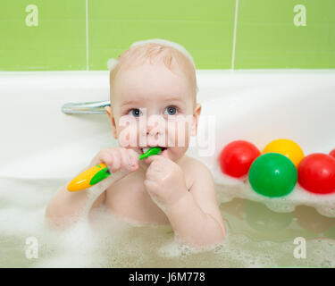 Cute child boy brushes teeth and smiles, sitting in bathtub - Stock Photo