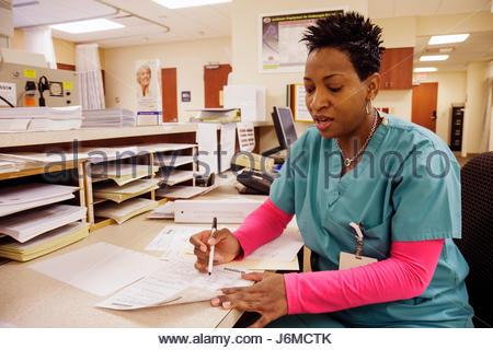 Miami Beach Florida Mt. Mount Sinai Medical Center hospital Black woman nurse technician taking writing information - Stock Photo