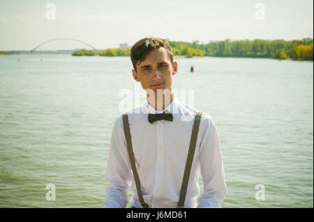 young skinny man, elegantly stylishly dressed in white shirt, gray trousers with suspenders and bow tie. guy sitting - Stock Photo