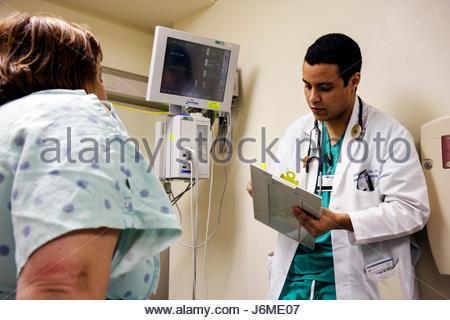 Miami Beach Florida Mt. Mount Sinai Medical Center hospital emergency room patient doctor Hispanic man chart interview - Stock Photo
