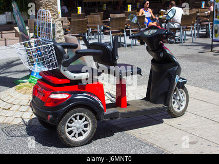 A battery powered disability scooter hired by a holiday maker in Playa Las Americas in Teneriffe in the Canary Islands - Stock Photo