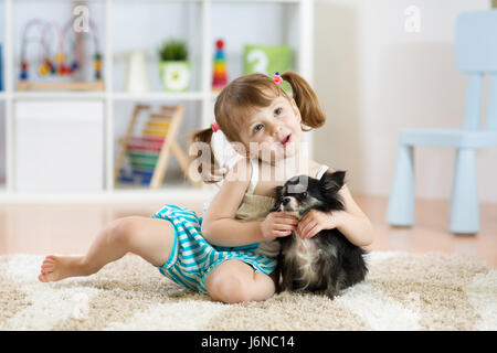 Lovely little girl playing with her pet dog - Stock Photo