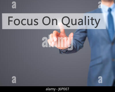 Focus On Quality - Businessman hand pressing button on touch screen interface. Business, technology, internet concept. - Stock Photo
