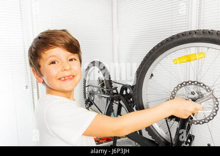 Close-up portrait of happy six years old boy repairing his bicycle wheel with spanner - Stock Photo