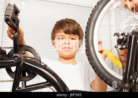 Close-up portrait of smiling six years old boy repairing his bicycle indoors - Stock Photo