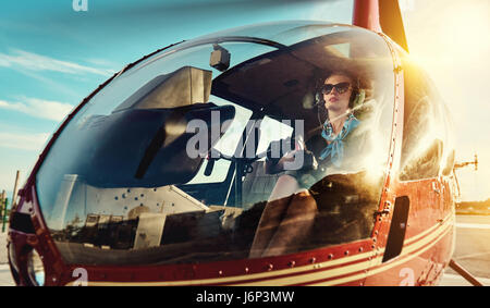 Attractive woman pilot sitting in the helicopter - Stock Photo