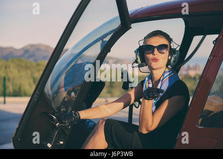 Attractive woman pilot sitting in the helicopter and blowing a kiss - Stock Photo