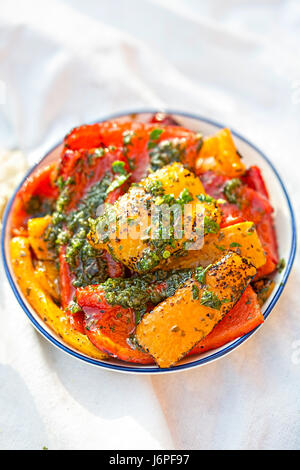 Antipasti - red, green and red peppers with green pesto - Stock Photo