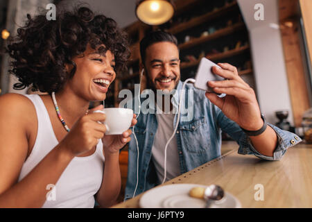 Young man showing something on cellphone to his girlfriend at cafe. Happy young couple sitting at coffee shop having - Stock Photo