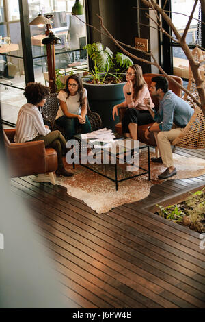 Vertical shot of corporate professionals discussing new ideas in office lobby. Creative business team meeting in - Stock Photo