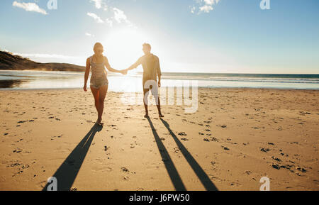 Outdoor shot of romantic young couple walking along the sea shore holding hands. Young man and woman walking on - Stock Photo