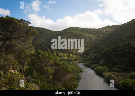 A beautiful natural river between the Italian mountains. River flowing into a beautiful beach in Sardinia. - Stock Photo