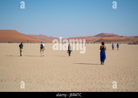 People Walking in the Desert, Sossusvlei Salt Pan Desert Landscape with Dead Trees, Namibia - Stock Photo