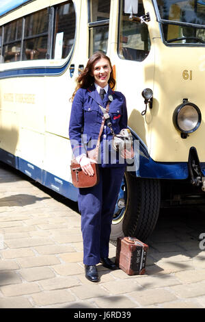 A young woman dresses up as a bus conductor for Haworth's 1940s weekend in Yorkshire. - Stock Photo