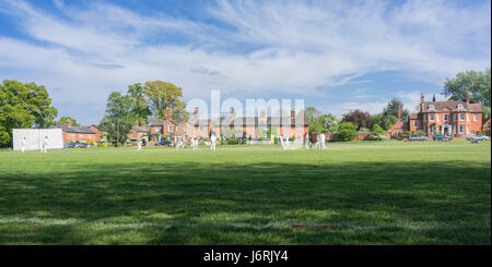 Village cricket being played on the green at Hartley Wintney in Hampshire, UK - Stock Photo