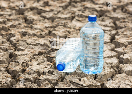 Bottle with water on the dried ground. Global drought, warming. Dried soil. - Stock Photo