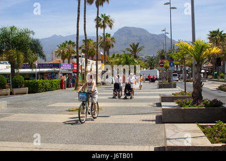 Tourists walking and cycling on a tree lined avenue with shops and cafes in Playa de Las Americas on the island - Stock Photo