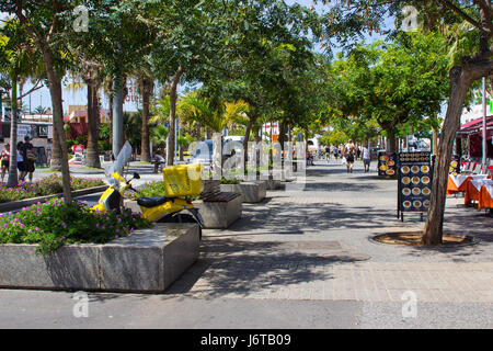 Tourists walking and dining on a tree lined avenue with shops and cafes in Playa de Las Americas on the island of - Stock Photo
