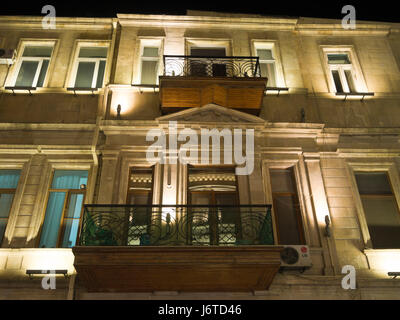 Night-time view of people and buildings in and around Nizami street, a shopping and pedestrian area in central Baku - Stock Photo