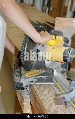 Male worker operatioing an industrial miter saw / chop saw. - Stock Photo