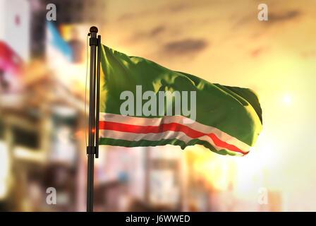 Chechen Republic of Ichkeria Flag Against City Blurred Background At Sunrise Backlight - Stock Photo