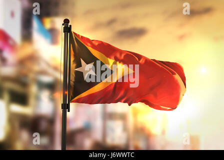 East Timor Flag Against City Blurred Background At Sunrise Backlight - Stock Photo