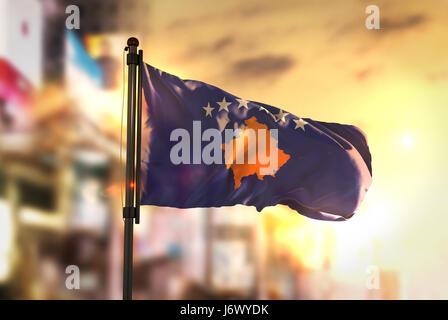 Kosovo Flag Against City Blurred Background At Sunrise Backlight - Stock Photo