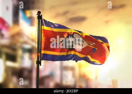 Swaziland Flag Against City Blurred Background At Sunrise Backlight - Stock Photo