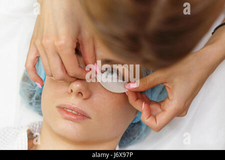 Beauty salon. Preparation of eyelashes of the lower eyelid before the procedure of eyelash extension. Shooting close - Stock Photo