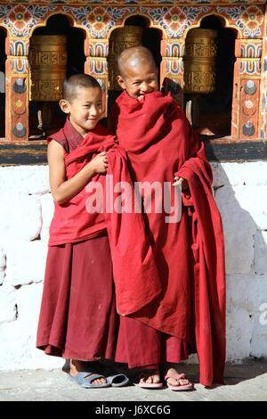 PARO, BHUTAN - NOVEMBER06,2012 : Unidentified smiling young monks standing by the religious prayer wheels at Paro - Stock Photo