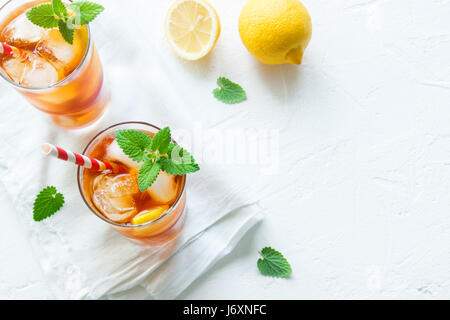 Iced tea with lemon slices and ice cubes on white rustic background close up. Homemade refreshing summer drink. - Stock Photo