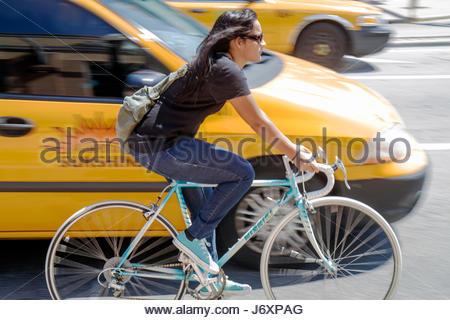 Miami Beach Florida Washington Avenue Hispanic woman bicycle biker bike no helmet - Stock Photo