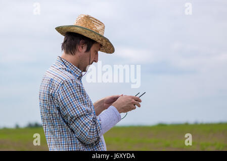 Smart farming concept, farmer using drone remote controller to navigate aircraft in cultivated field and examine - Stock Photo