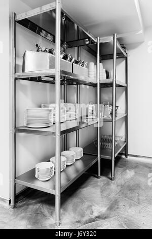 Stainless steel rack of kitchenware holding utensils, dishes, small kitchen appliances in a household or kitchen. - Stock Photo